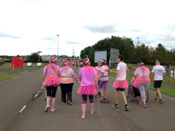 Finish in site! Typical of her, Deb's tutu is tucked in her trousers! Left to right: Sare, Giggler, Angie, Matthew, Sharon, Lewis, Deb pushing me in Wilma, Adam *Photo courtesy of Jazz & team*